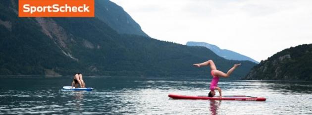 Zwei Frauen machen Yoga auf einem Surfboard.