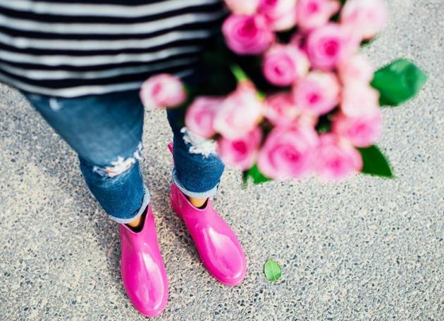 Frau in rosa Gummistiefeln mit Strauß rosa Rosen in der Hand