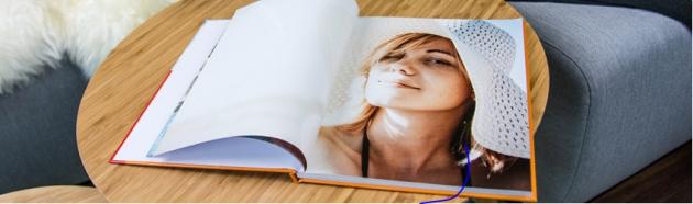 Aufgeschlagenes Fotobuch mit Frauenbild liegt auf einem Tisch.