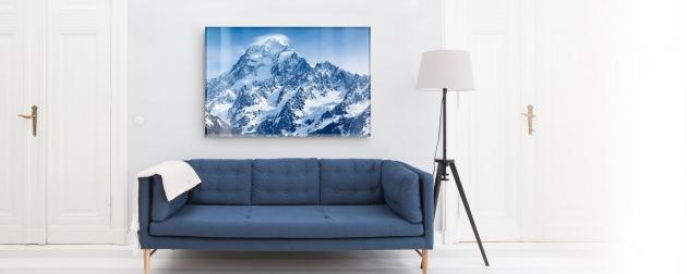 Bild mit Bergen an der Wand und davor eine blaue Couch