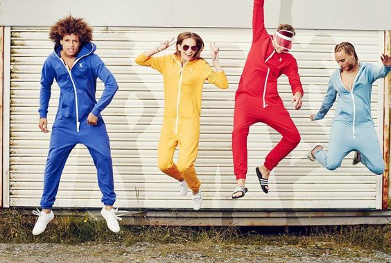 Vier Models in blauem, gelbem, rotem und hellblauem Jumpsuite hüpfend