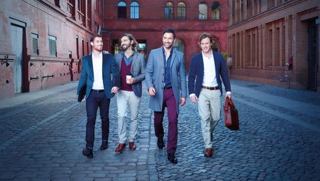 Vier Herren laufen eine Straße entlang